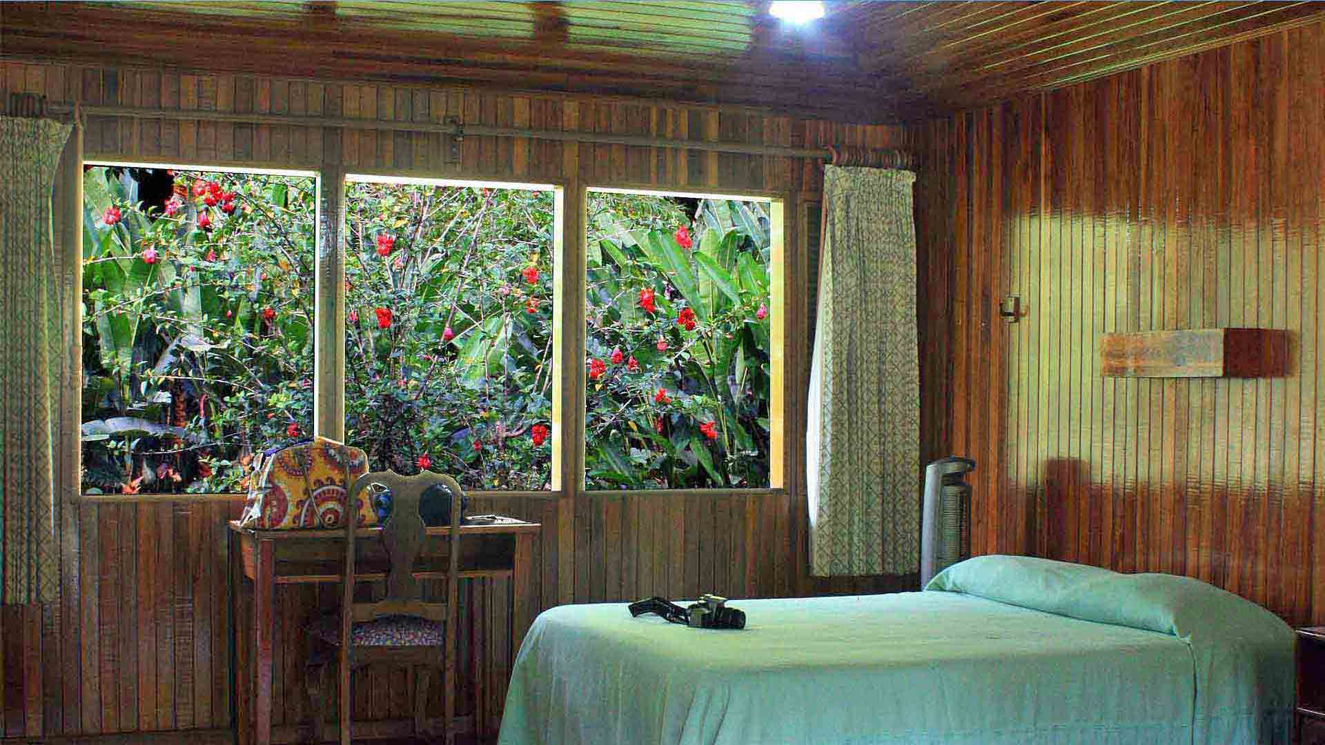 Wood-paneled Bedroom with Screened Window and Flowers