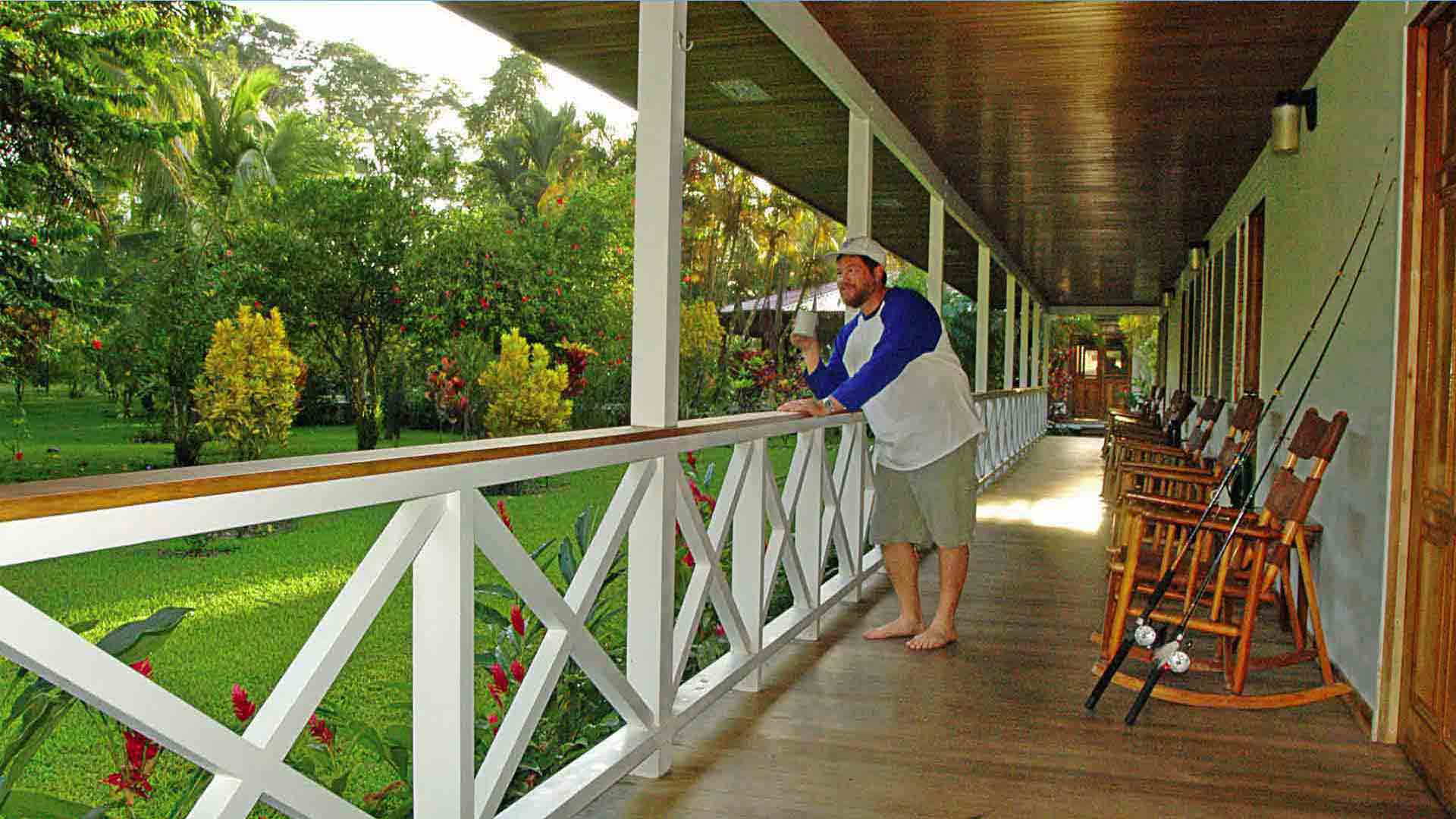 Angler with Cup of Coffee on the Porch Overlooking Flowers
