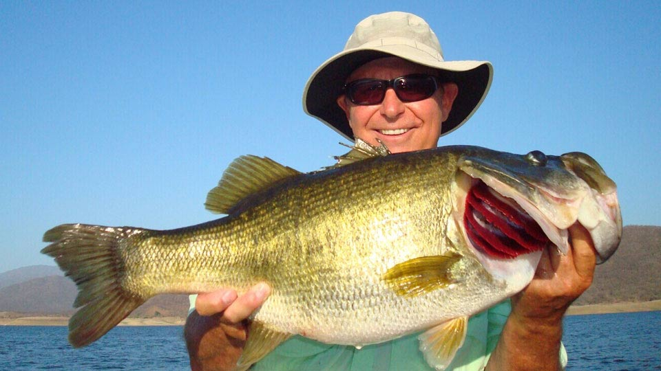 Angler with floppy hat and huge largemouth bass