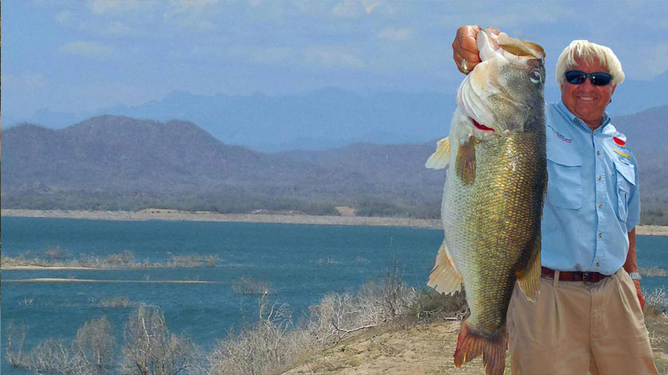 Angler holding up Largemouth bass with Sierra Madres in background