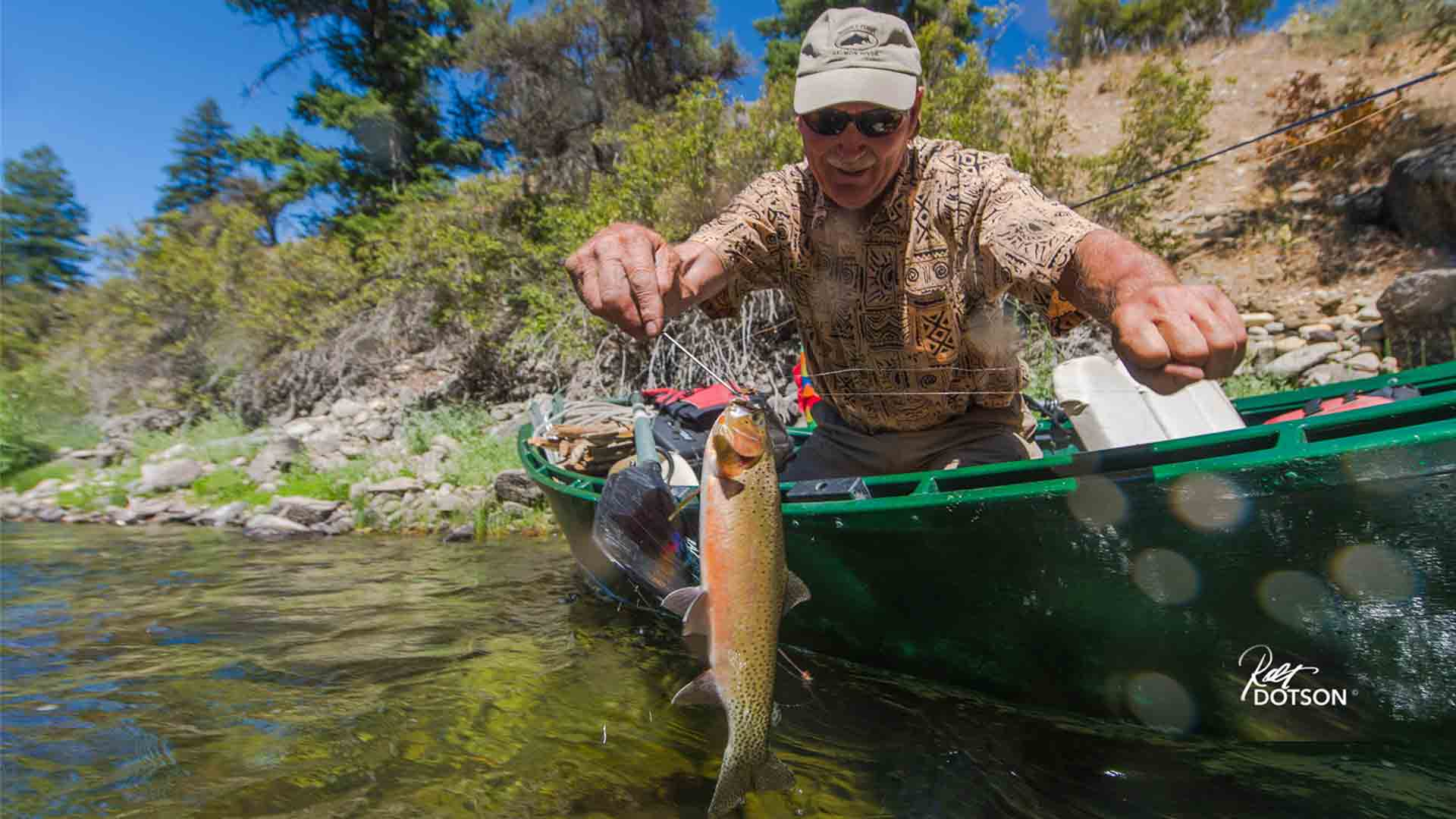 Angler leaning over side of Drift Boat with Cutthroat